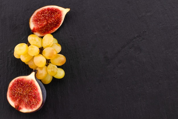 Свежие спелые инжир и виноград на темном фоне, вид сверху с копией пространства