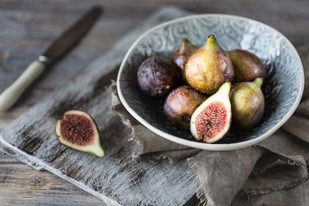 Fresh ripe figs in a bowl on a dark wooden table. selective focus