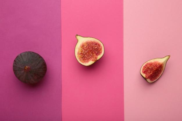 화려한 분홍색 배경에 신선한 익은 무화과. 열대 과일