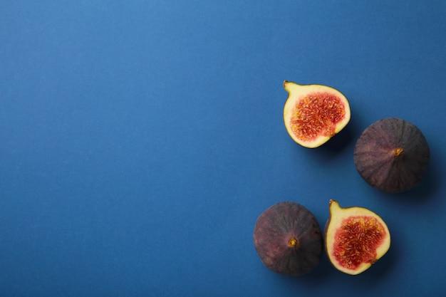 진한 파란색 배경에 신선한 익은 무화과. 열대 과일