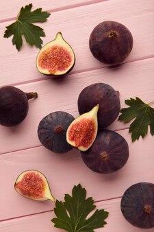분홍색 나무 바탕에 신선한 익은 무화과. 열대 과일
