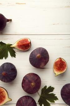 흰색 나무 바탕에 신선한 익은 무화과. 열대 과일