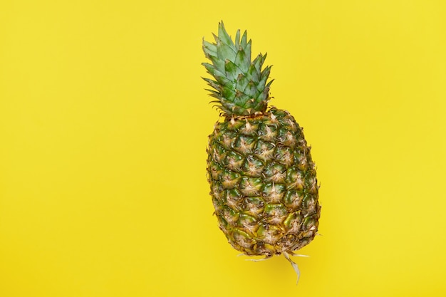 Fresh ripe flying pineapple on a yellow background. summer concept. copy space, minimalism.