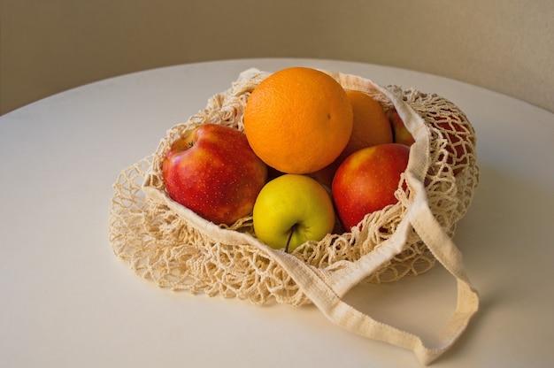 環境にやさしいナチュラルバッグに入った新鮮な熟した果物。プラスチックなし、ゼロウェイストのコンセプト。持続可能なライフスタイルのコンセプト