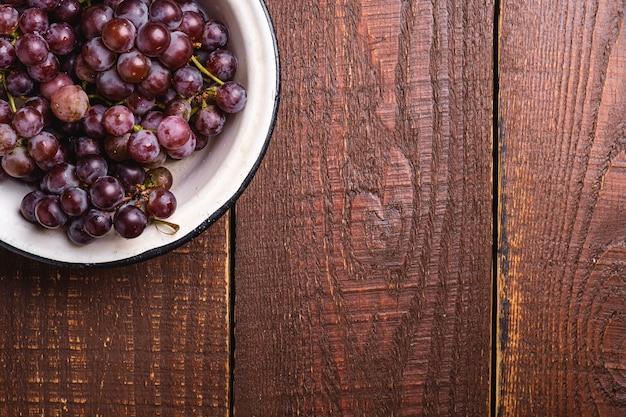 Свежие спелые ягоды винограда в миске на коричневом деревянном фоне, вид сверху копией пространства