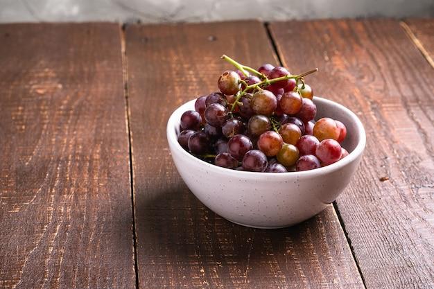 Свежие спелые ягоды винограда в миске на коричневом деревянном столе, угловой вид