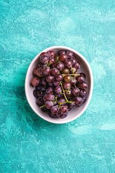 Свежие спелые ягоды винограда в миске на бирюзовом текстурированном фоне, вид сверху