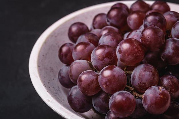Свежие спелые ягоды винограда в белой деревянной миске на темном каменном столе, макрос углового обзора