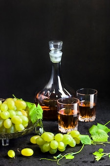 Fresh ripe grapes in a fruit bowl and decanter and two glasses with grape juice on black background