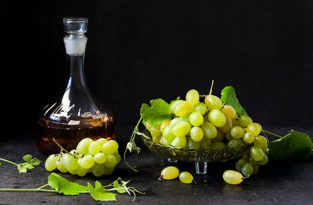 Fresh ripe grapes in a fruit bowl and decanter with grape juice  on black background