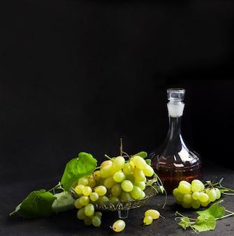 フルーツボウルとデカンターで新鮮な熟したブドウと黒の背景にブドウジュース。コピースペース