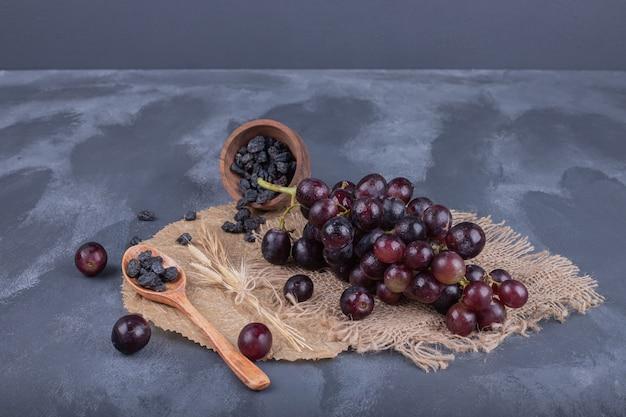 Uva fresca e matura e cucchiaio su tela da imballaggio.