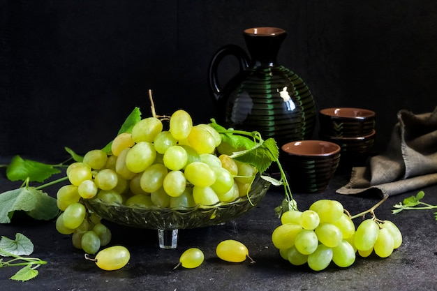 Fresh ripe grapes with leaves in a fruit bowl and ceramic jar and glasses on black background