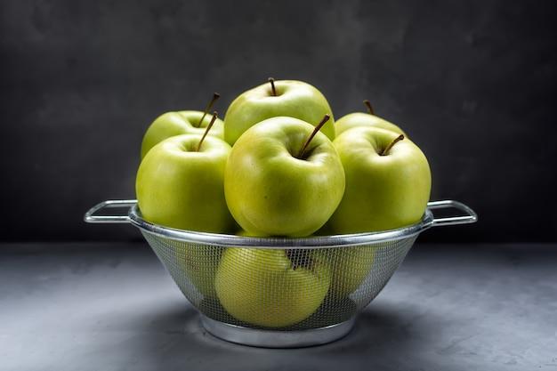 金属ザルに新鮮な熟した青リンゴ