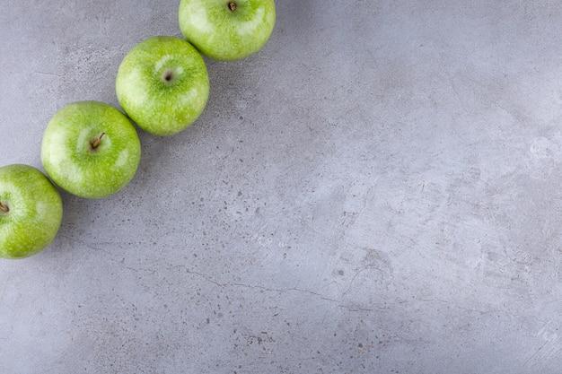 Свежие спелые зеленые яблоки на камне.
