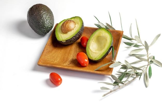 Свежий спелый зеленый авокадо с маленькими помидорами черри на блюде и на белом фоне.