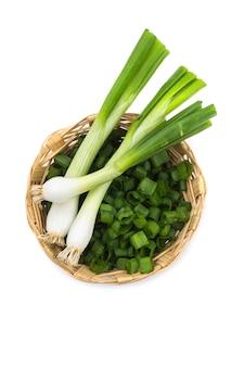 Свежий спелый зеленый лук (лук-шалот или лук) с нарезанным луком в корзине