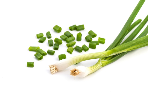 Fresh ripe green spring onions (shallots or scallions) with fresh chopped green onions on white surface