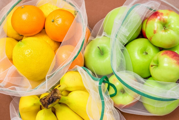 Fresh ripe and juicy fruits in reusable eco-friendly mesh bags.