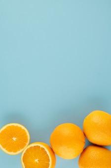 밝은 파란색 배경에 신선한 익은 달콤한 오렌지. 여름, 수확, 비타민 개념