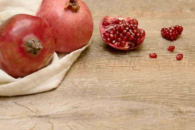新鮮な熟したジューシーなザクロとシードバッグ横になっているテーブルウッドの健康的な果物ビーガンベジタリアン料理