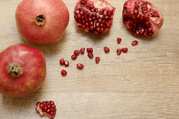 テーブルの上に横たわっている新鮮な熟したジューシーなザクロと種子健康的な果物ビーガンベジタリアン料理
