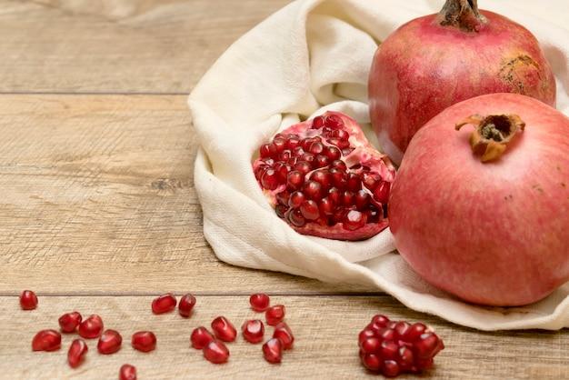 新鮮な熟したジューシーなザクロの種バッグテーブル木製の背景果物ビーガンベジタリアン料理