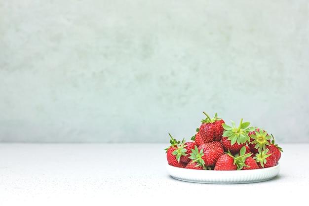 白いボウルに新鮮な熟したジューシーな赤いおいしい有機イチゴ