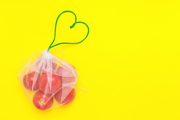 Fresh ripe and juicy tomatoes in reusable eco-friendly mesh bag on the yellow.