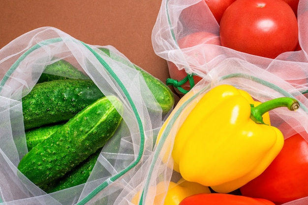 Fresh ripe and juicy vegetables in reusable eco-friendly mesh bags.