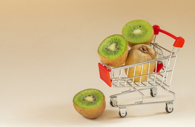 Fresh ripe kiwi in supermarket cart. space for text