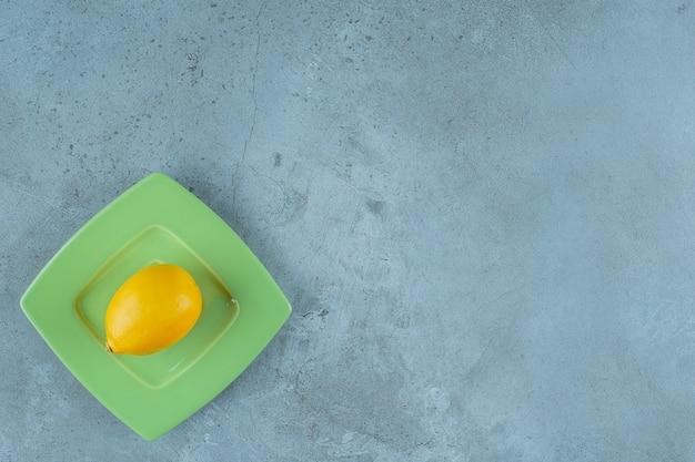 Fresh ripe lemon on a coaster, on the marble background.
