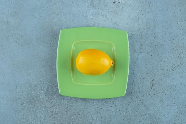 대리석 배경에 코스터에 신선한 익은 레몬. 고품질 사진