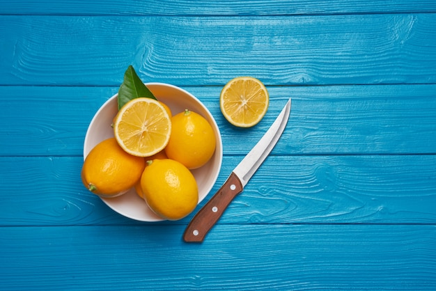 Свежие спелые лимоны и нож на синий деревянный стол. вид сверху с копией пространства.