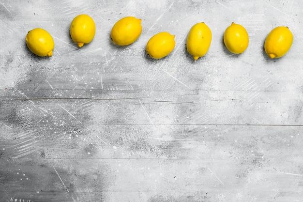 新鮮な熟したレモン。素朴な背景に