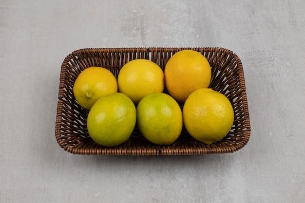 Свежие спелые лимоны на деревянной корзине.