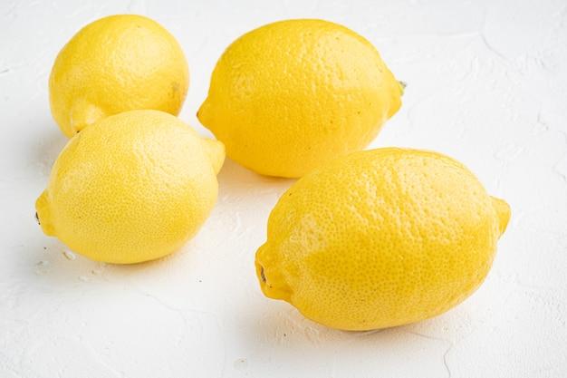 흰 돌 테이블 배경에 신선한 익은 레몬 세트