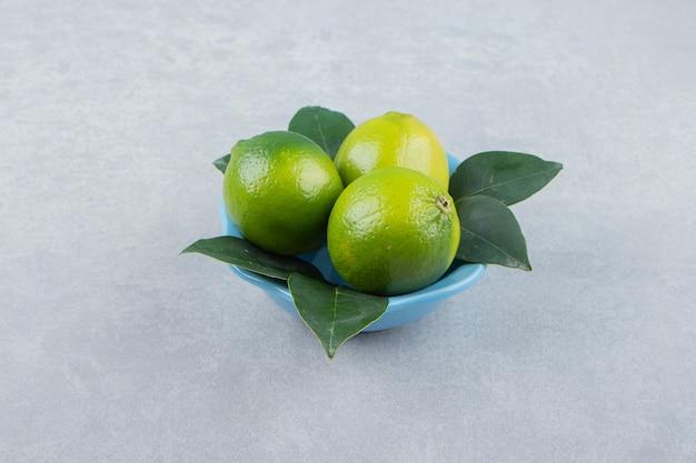 Fresh ripe limes in blue bowl