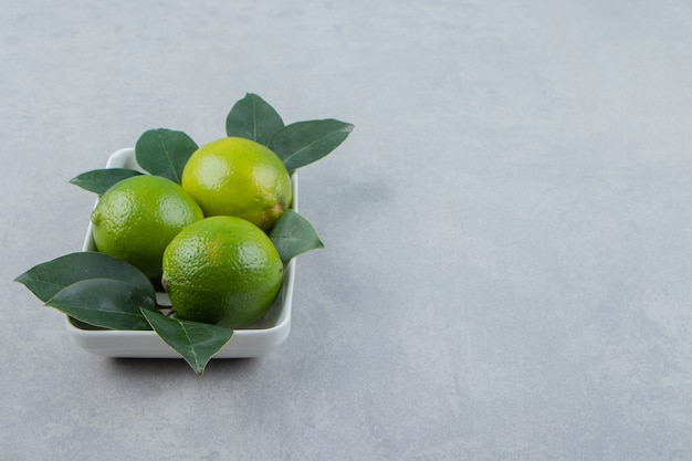 Свежие спелые лаймы на белой тарелке