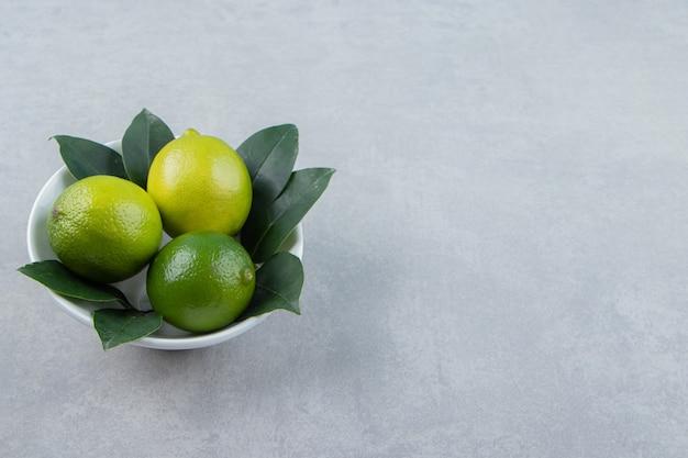 Fresh ripe limes in white bowl.