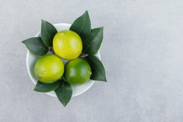 Fresh ripe limes in white bowl