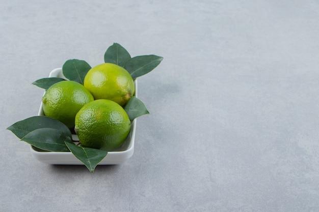 Fresh ripe limes on white plate