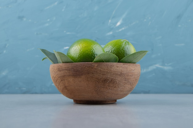 Fresh ripe limes in wooden bowl.