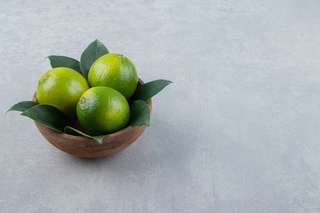 Fresh ripe limes in wooden bowl