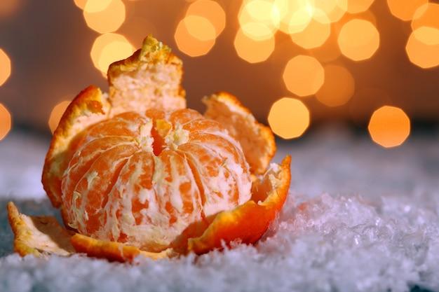 Свежий спелый мандарин на снегу, на фоне огней