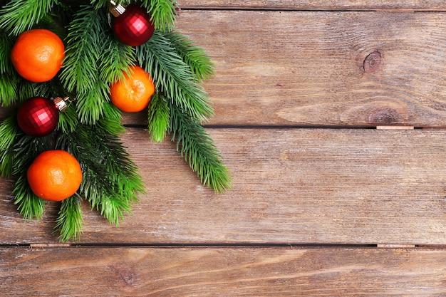 Свежие спелые мандарины и бутон ели на деревянных фоне