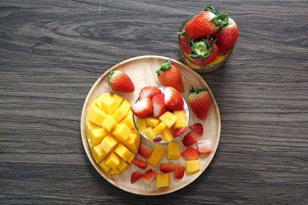 나무 접시에 쿠키 간장 요구르트와 함께 컵에 신선한 익은 망고와 딸기 과일