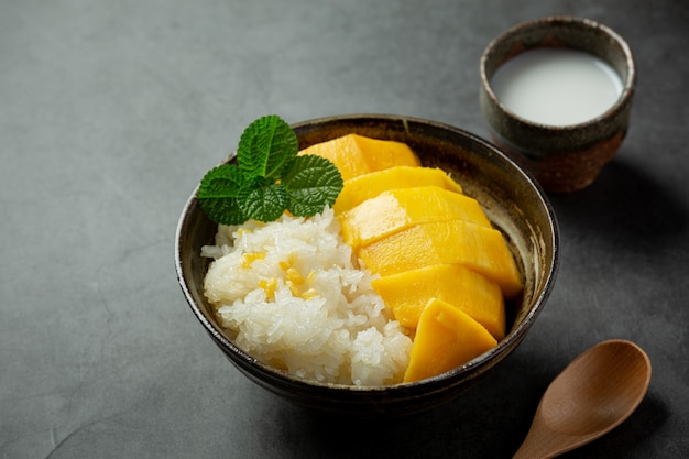 Fresh ripe mango and sticky rice with coconut milk on dark surface