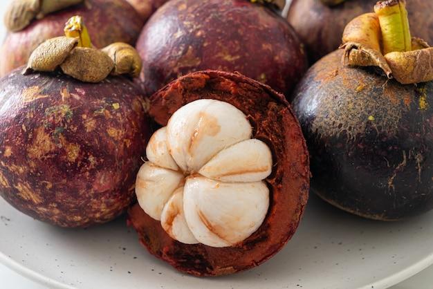 Свежие спелые плоды мангустана на белой тарелке