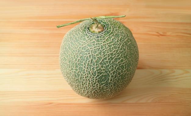 木製のテーブルに茎を持つ新鮮な熟したマスクメロンまたはマスクメロンの果実